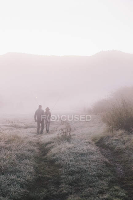 Man and woman walking in a frosty morning. — Stock Photo