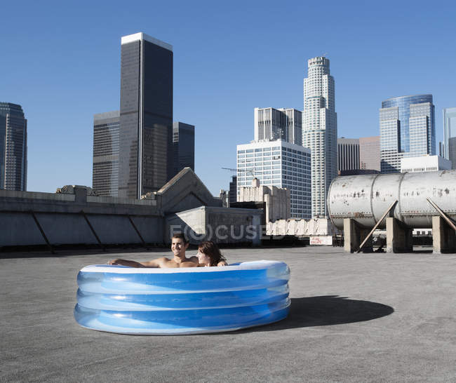 Пара в надувном бассейне на городской крыше — стоковое фото