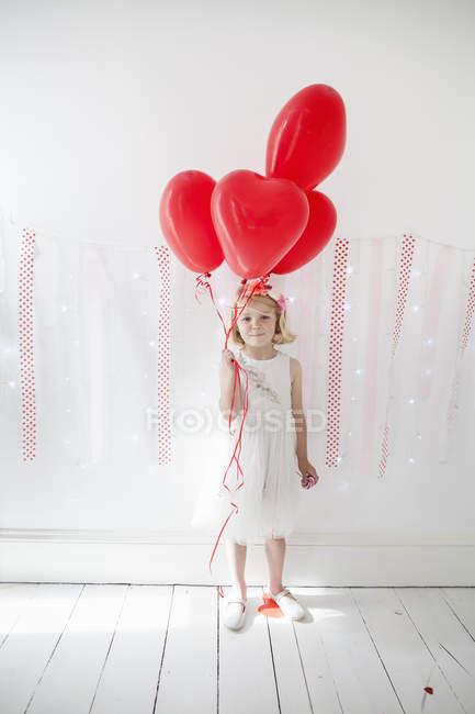 Junges Mädchen halten rote Ballons — Stockfoto