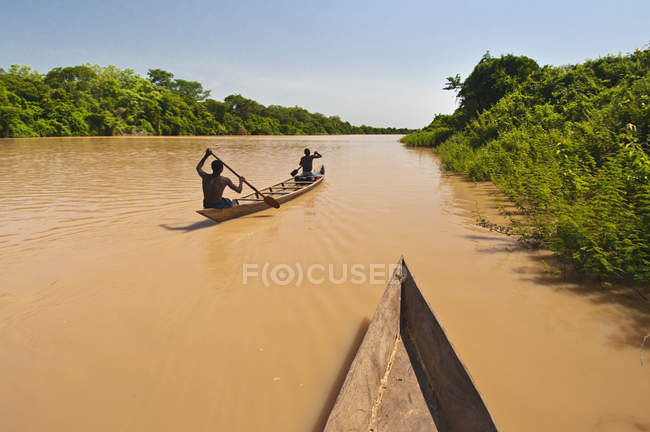Hombres remando canoa aguas arriba - foto de stock