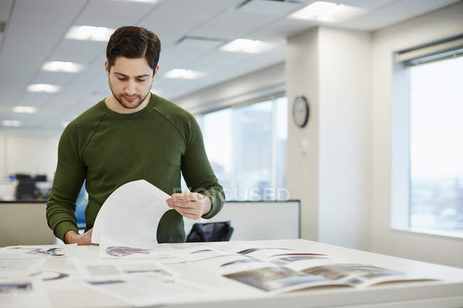 Man in an office checking proofs — Stock Photo