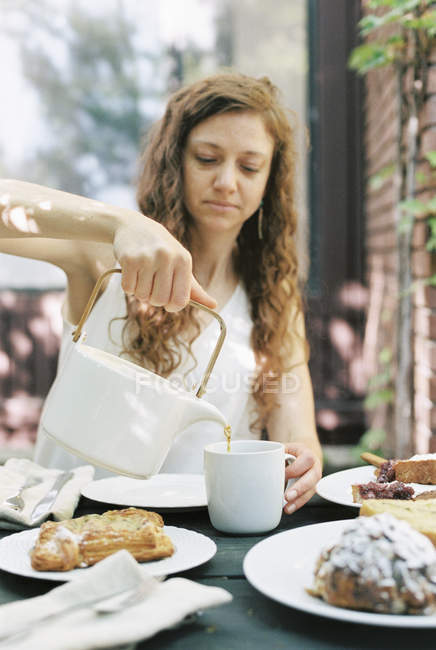 Woman pouring a cup of tea. — Stock Photo