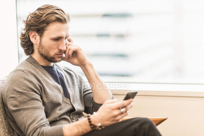 Bearded man sitting frowning — Stock Photo