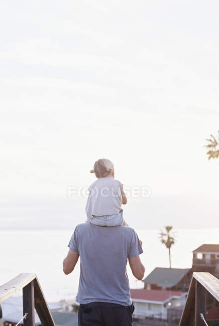 Man carrying daughter on his shoulders. — Stock Photo