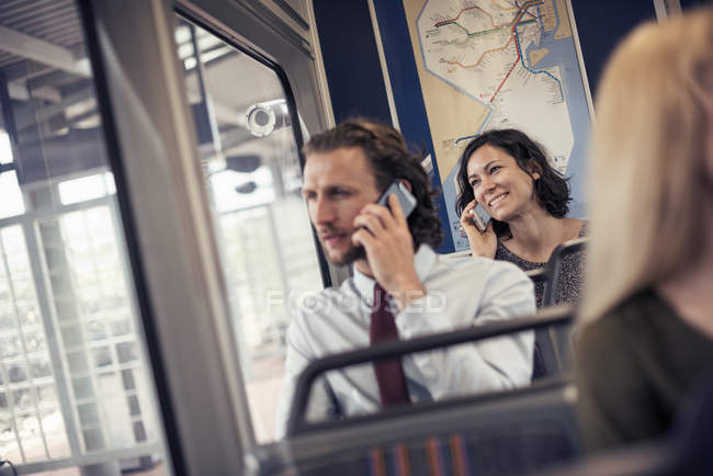 People seated on a bus talking on phones — Stock Photo
