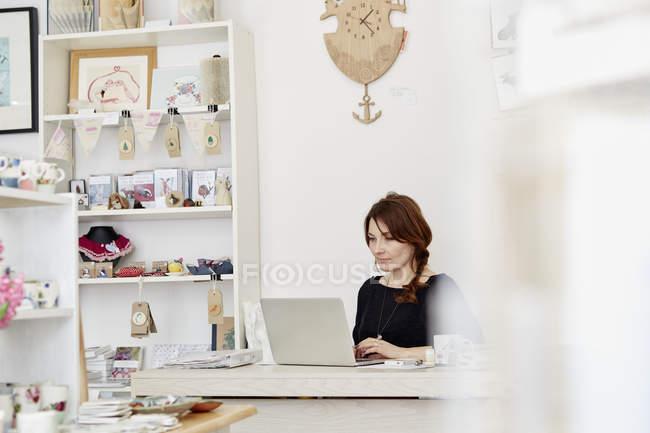 Жінка, сидячи за столом, використовуючи ноутбук — стокове фото