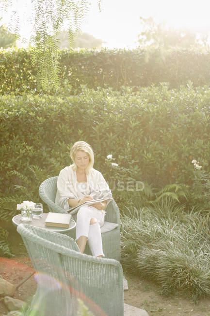 Femme assise dans un jardin — Photo de stock