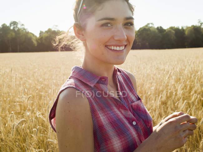 Frau steht in einem Weizenfeld — Stockfoto