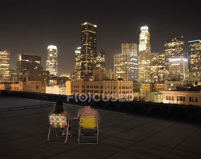 Pareja en una azotea con vistas a la ciudad por la noche - foto de stock