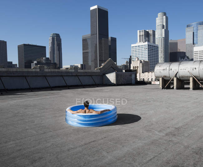 Man in inflatable pool on a city rooftop — Stock Photo