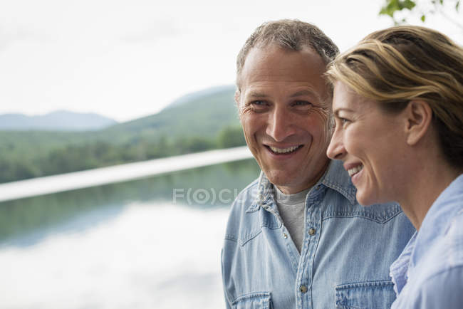 Couple standing by lake shore — Stock Photo