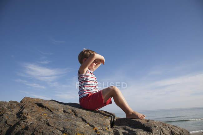 Enfant assis sur les rochers — Photo de stock
