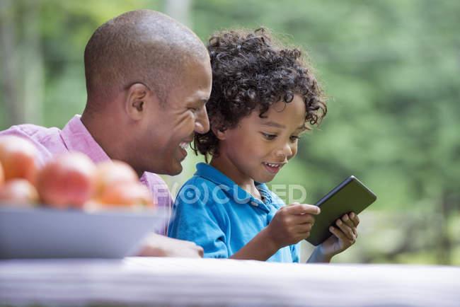 Padre e hijo con teléfono inteligente - foto de stock