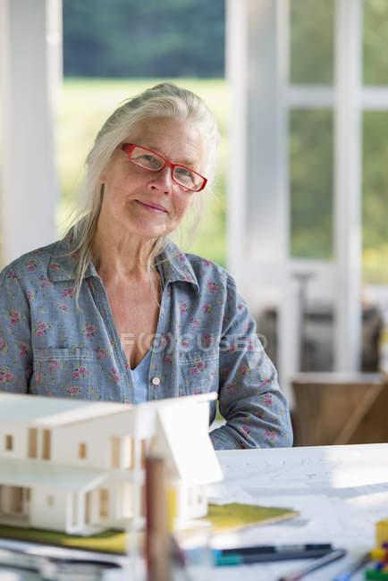Зрелая женщина проектирует дом — стоковое фото
