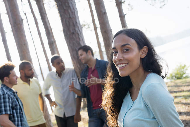 Friends gathered in shade of pine trees — Stock Photo