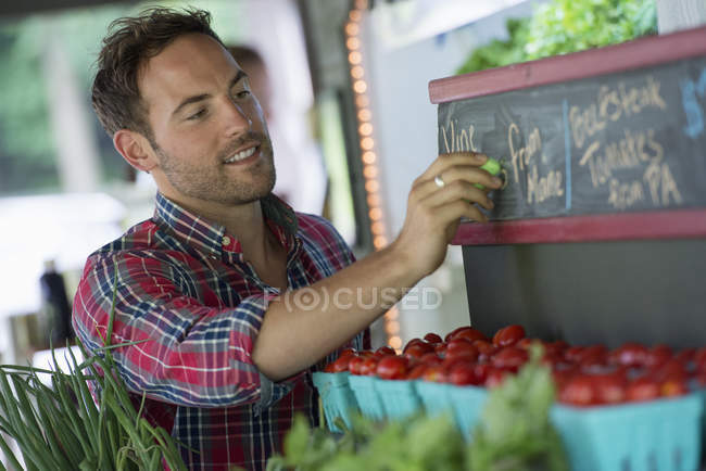 Man chalking up prices on the blackboard — Stock Photo