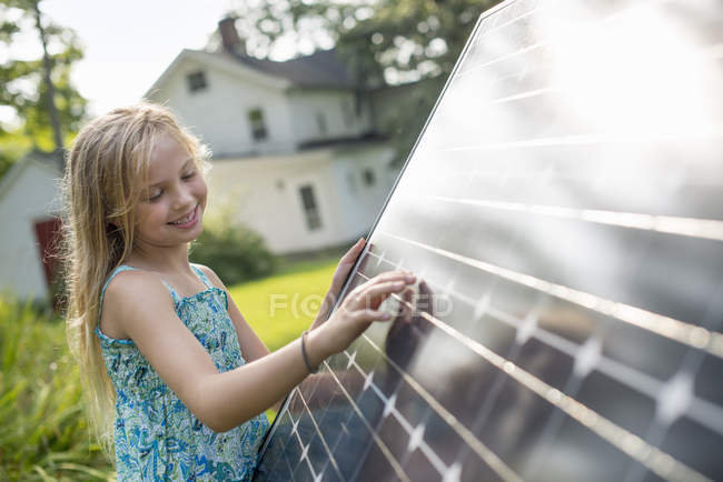 Girl beside a large solar panel — Stock Photo
