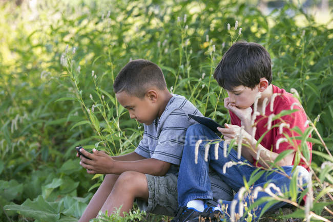 Boys using smartphone and digital tablet. — Stock Photo
