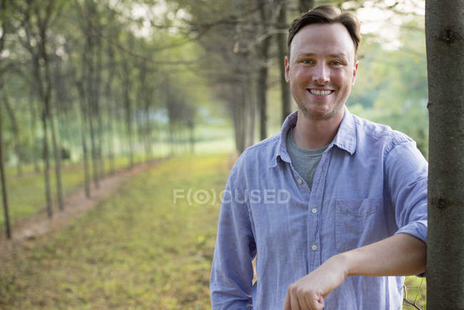 Man leaning against a tree — Stock Photo