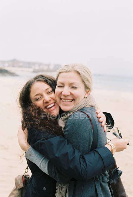 Women cheek to cheek hugging — Stock Photo