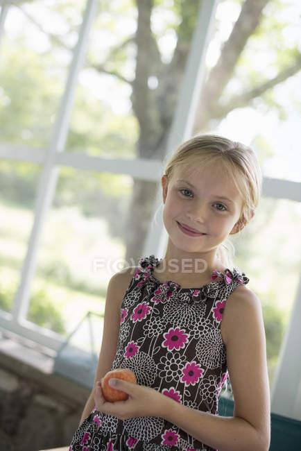 Girl holding a peach fruit — Stock Photo