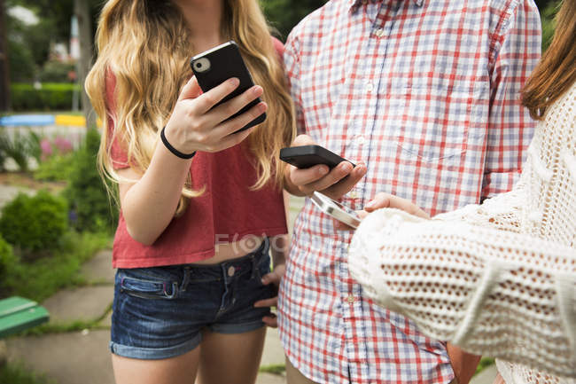 Friends looking at phones — Stock Photo