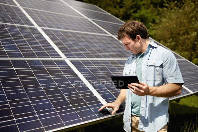 Farmer closely inspecting a solar panel — Stock Photo