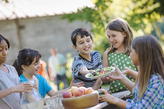 Дети едят свежие fruitss и салаты — стоковое фото