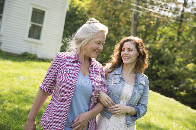 Women walking in the yard near the house — Stock Photo