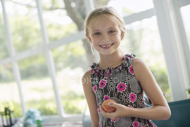 Girl holding a peach fruit — Stock Photo