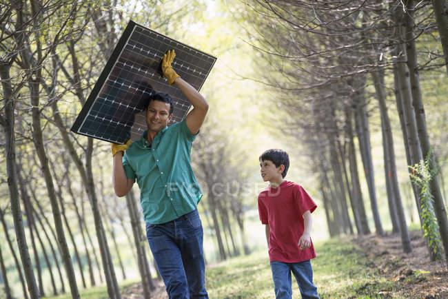 Людина, несучи панелі сонячних батарей — стокове фото