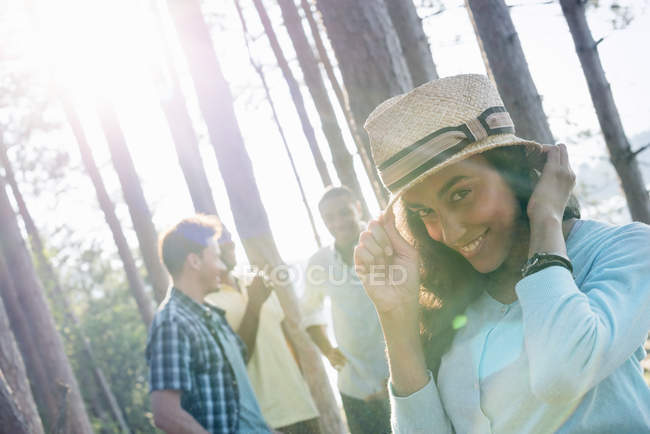 Friends gathered in the shade of pine trees — Stock Photo