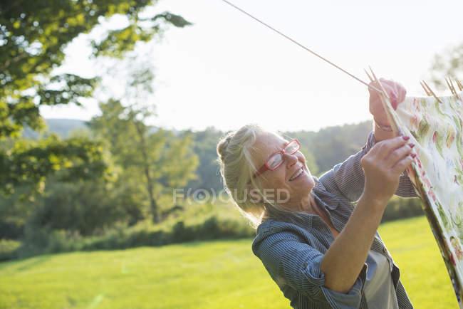 Женщина висит прачечная на стиральной линии — стоковое фото