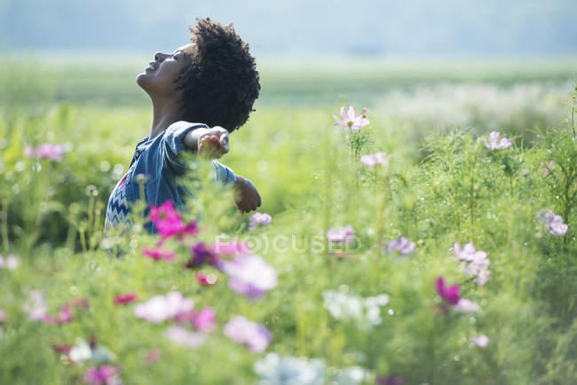 Frau stehend unter Blumen — Stockfoto
