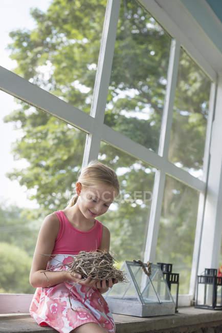 Girl Holding a bird nest. — Stock Photo
