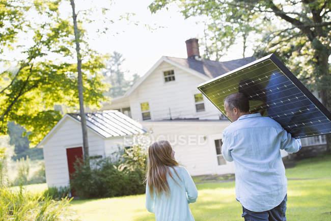 Uomo che trasporta pannello solare — Foto stock