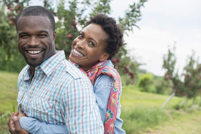 Casal abraçando e sorrindo para a câmera — Fotografia de Stock
