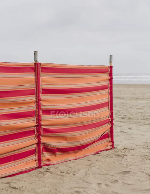 Red striped windbreak on Beach — Stock Photo
