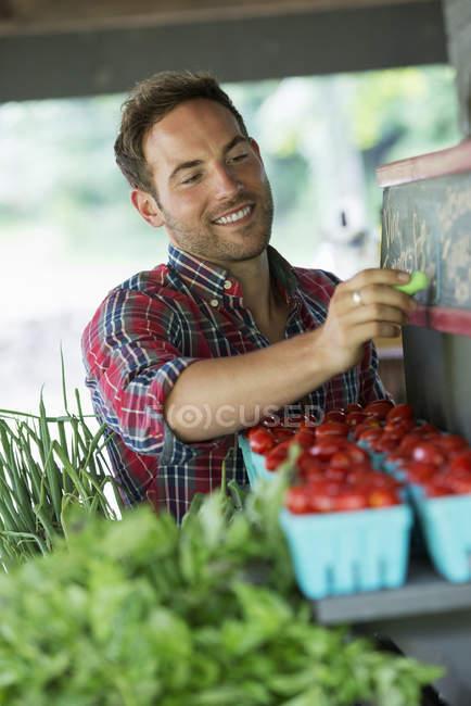 Uomo sfarinamento i prezzi sulla lavagna — Foto stock