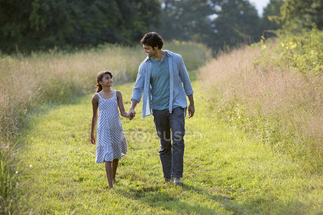 Man and girl walking down mown path — Stock Photo