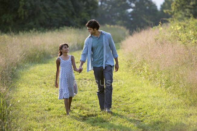 Uomo e ragazza che camminano lungo il sentiero falciato — Foto stock