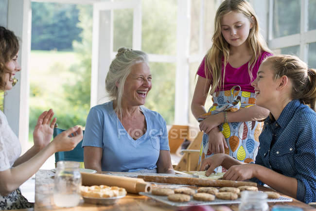 Four generations of women baking together. — Stock Photo