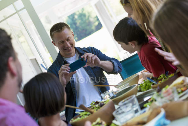 Familienfest rund um einen Tisch in einem café — Stockfoto