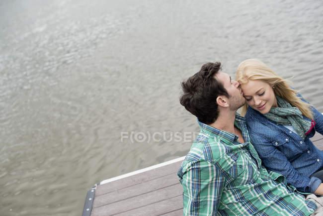 Мужчина и женщина сидят на пристани у озера . — стоковое фото