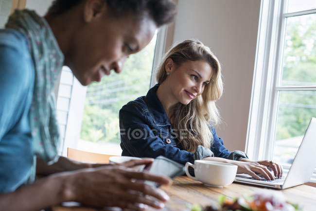 Women using a digital tablet and laptop. — Stock Photo