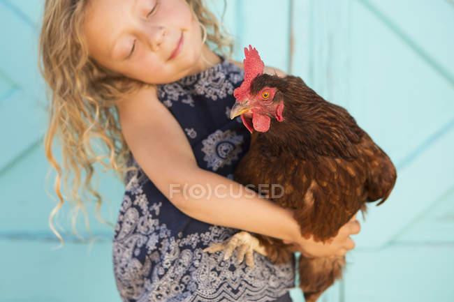 Girl holding chicken — Stock Photo