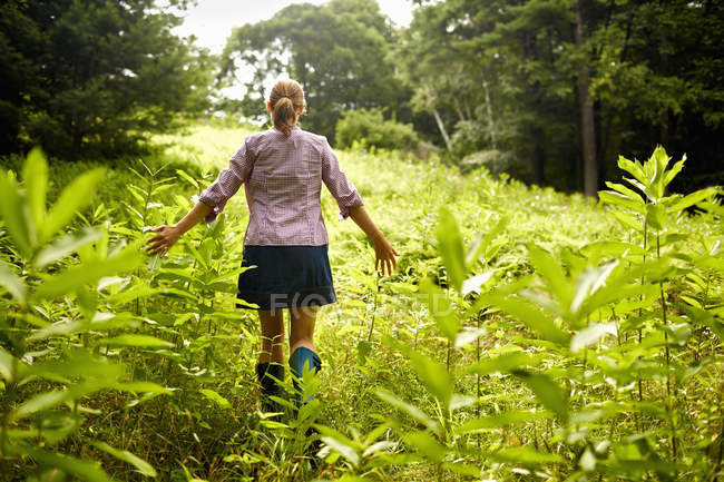 Woman walking through the undergrowth in woodland — Stock Photo