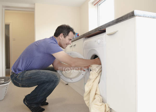 Homme lave-linge dans la machine à laver . — Photo de stock