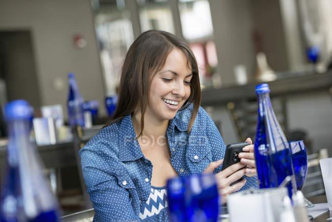 Женщина, используя смартфон в ресторане — стоковое фото