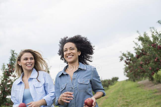Mulheres carregando maçãs em suas mãos — Fotografia de Stock